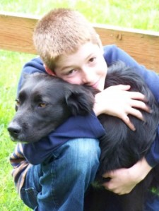 Picture of a boy and his rescued dog hugging.