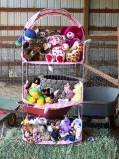 Picture of 3 tiered shelf of stuffed animal prizes.