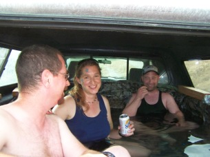 Picture of three people in a pool made from the back of a truck.