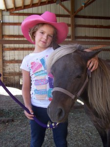 Picture of a girl in a cute pink cowgirl hat with Trigger.