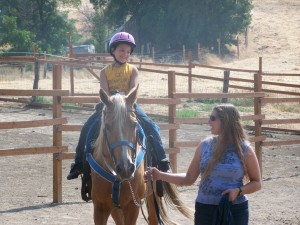 Picture of a boy smiling during his first horse back ride.